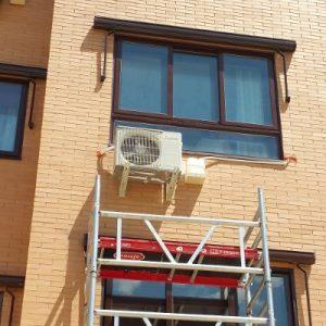 Instalación de aire acondicionado en una vivienda a varias alturas con andamio.