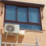 Compresor exterior con garrafa para la evacuación del agua en una instalación de aire acondicionado en Fuenlabrada, Madrid.